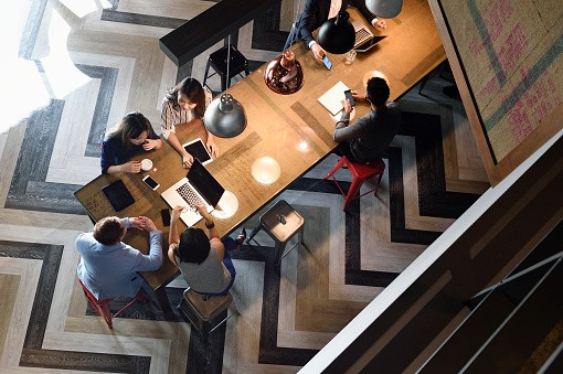 Young Chinese colleagues working together in a busy co-working space from above