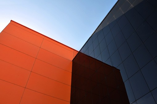 Black and orange modern buildings reflect each other. View from below.