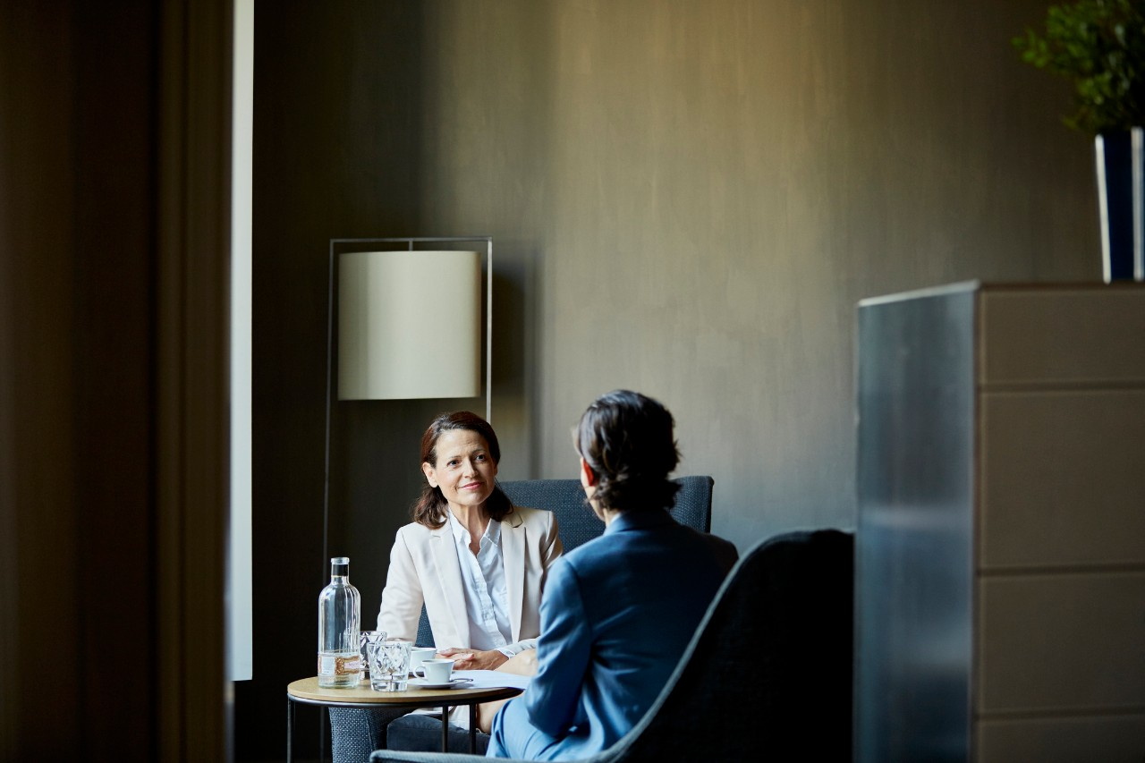 Smiling businesswoman in meeting while sitting on chairs at hotel room